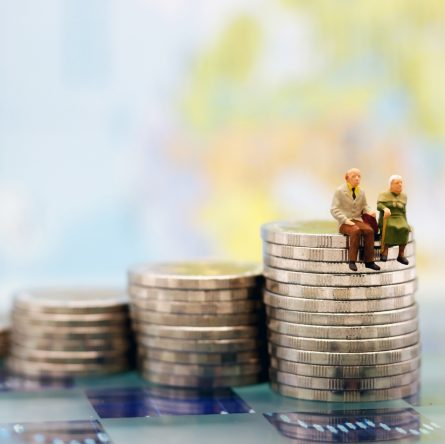 Miniature people: Happy senior couple sitting on coins stack, money saving growth. Retirement, emergency plan and Financial Concept.
