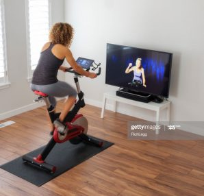 A woman exercising on a spin bike using an online instructor inside a home.